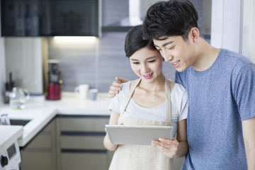 Young couple a using digital tablet in the kitchen