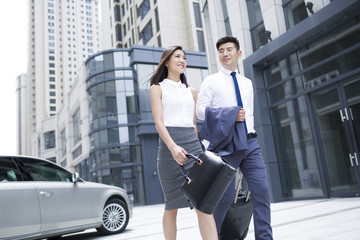 Confident business people walking with wheeled luggage
