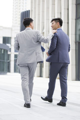 Confident businessmen talking and walking outdoors