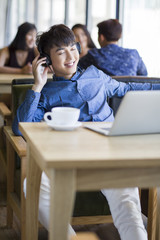 Young man listening to music in caf¨_