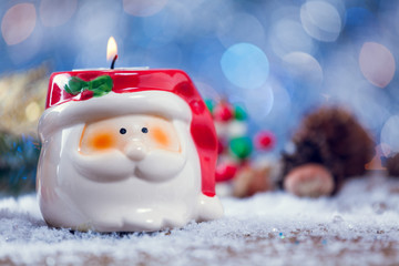 Santa Claus Candle Holder On Snowy Wooden Background.