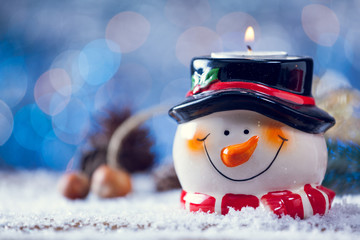 Snowman Candle Holder On Snowy Wooden Background.