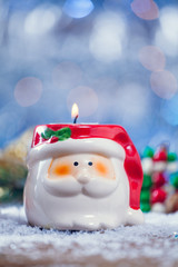 Santa Claus Candle Holder On Snowy Wooden Vertical Background.