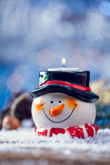 Snowman Candle Holder On Snowy Wooden Vertical Background.