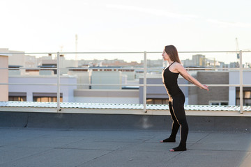 Young woman doing yoga on the roof