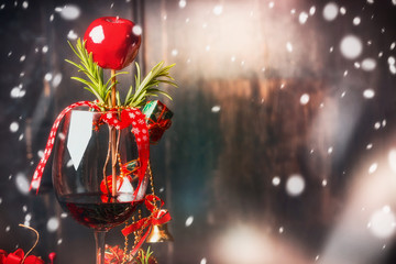 Red wine glass with Christmas decoration at dark wooden background with snow