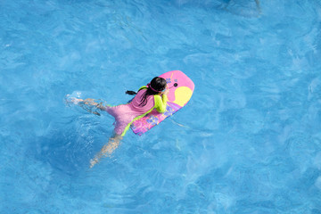 girl is swimming with swimming board from top view