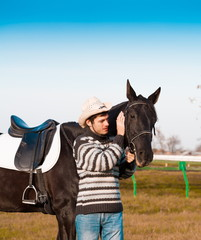 Man nearby horse, striped pullover, blue jeans, hat, close up