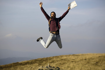 Man hipster jumps with map
