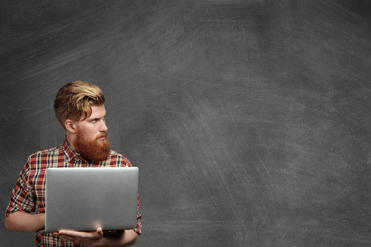Young bearded school teacher with stylish haircut dressed in red checkered shirt using laptop computer while working in classroom after lessons, checking papers, looking away with serious expression