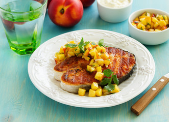 Slice the fish grilled with peach salsa.