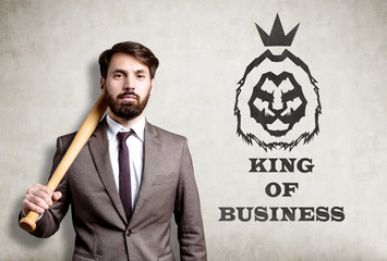 Portrait of bearded businessman with baseball bat near concrete