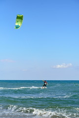 A man in a wetsuit floating on a Board with a kite