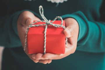 Woman hands holding a Christmas gift red box. Christmas presents and New Year. Handmade.