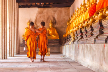 Two novices walking return and talking in old temple at sunset time, Ayutthaya Province, Thailand