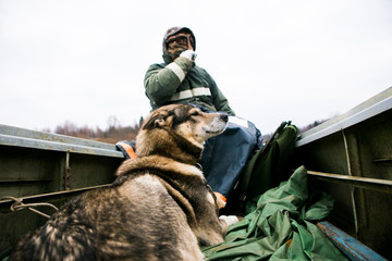 Male hunter swims on a boat with a hunting dog. Cold weather. A man dressed in a warm jacket and hat. Big gray dog Laika.