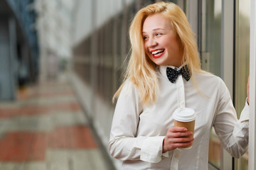 Laughing ginger girl with coffee cup standing in hall