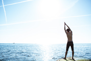 Young Male makes yoga exercise on the sea stone