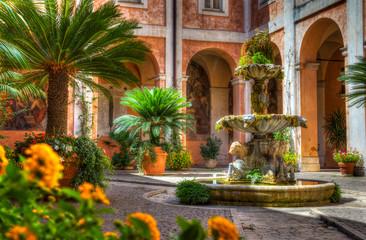Ein idyllischer, mediteran bewachsener Hinterhof mit einem zentralen Wasserspiel.  An idyllic, mediterranean overgrown backyard with a central water feature.