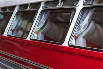 Part of red retro bus with passenger seats.