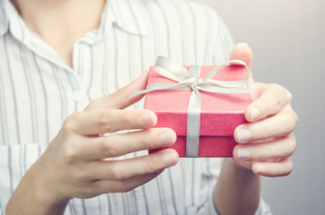 Closeup, Hand holding red gift box, female giving gift, New year holidays and greeting season concept.