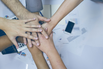 Multiethnic group of young people putting their hands on top of each other. Close up image of young students making a stack of hands with business report background