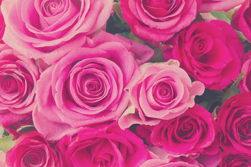 round bouquet of pink and magenta roses close up background, retro toned