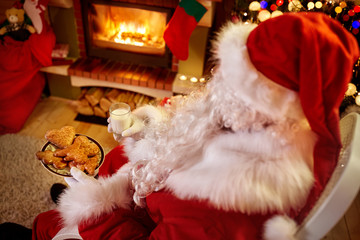 Santa Claus relaxing at home with milk and fresh cookies