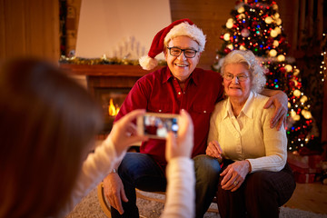 girl with smartphone taking picture grandparents on Christmas .