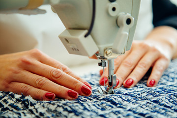 Women's hands at work with sewing machine