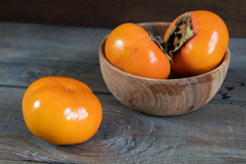 Fresh persimmons fruit in bowl on dark wooden background