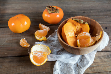Fresh persimmons and tangerines fruits in bowl on dark wooden background