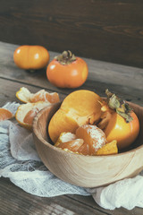 Fresh persimmons and tangerines fruits in bowl on dark wooden background. Coloring and processing photo