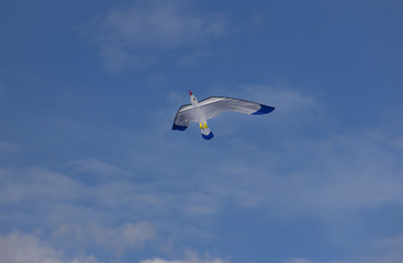 kite in the shape of a stork flying in a blue sky on a background of clouds