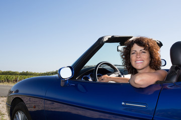 Woman in cabriolet car in happy and smiling