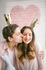 Young couple with crowns kissing in decorated studio