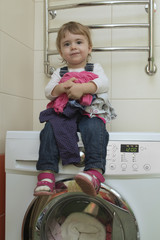 Happy cute little girl with clothes sitting on the washing machine in home interior