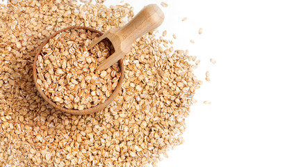 Heap of oats in wooden bowl and scoop. Premium oat flakes on white background