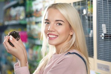 Portrait of beautiful young woman holding hamster in pet shop