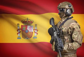 Soldier in helmet holding machine gun with flag on background series - Spain