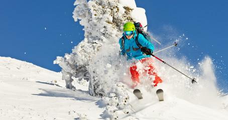 Freeride skier in powder snow running downhill