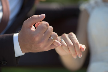 Groom and bride making a pinkie promise