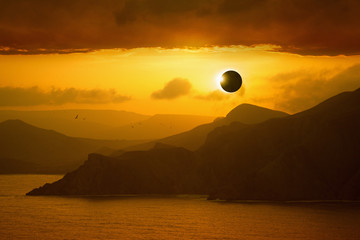Total solar eclipse, silhouettes of mountains in red glowing sky
