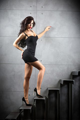 Fototapete - Sexy brunette woman staying on stairs
