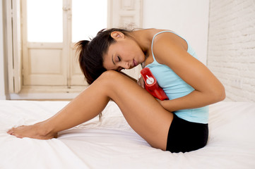 young beautiful hispanic woman holding hot water bottle against belly suffering menstrual period pain
