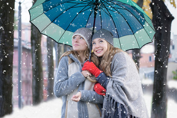 best friends, 2 girls in winter clothes with one umbrella during snowfall in cold winter season.