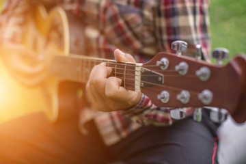 Young hipster man playing guitar to relaxing on his holiday, enj