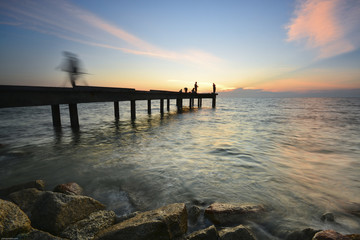 Beautiful dusk sky over the long jetty with silhouette of anglers. Long exposure shot of seascape.