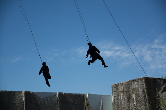 Men and women flying in sky with safety rope.