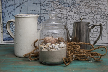 Nautical life style items: a Pitcher, a jar of seashells, a rope on a background map of the world.